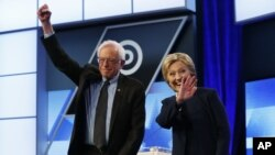 Kandidat Capres AS dari partai Demokrat, Hillary Clinton (kanan) dan Senator Bernie Sanders, menyambut para pendukungnya sebelum memulai debat di Miami-Dade College, Florida (9/3).