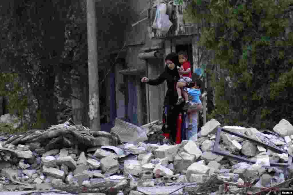A woman carries her child as she walks on rubble in a neighbourhood in Deir al-Zor, Syria, April 15, 2013.
