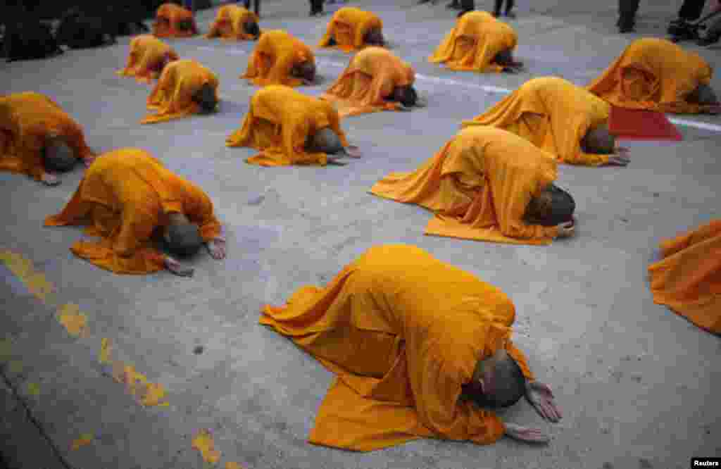 "Buddhist monks prostrate as they perform the ""three steps one bow"" ceremony at Kong Meng San Phor Kark See Monastery on the eve of Vesak Day in Singapore May 12, 2014."