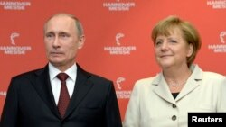 German Chancellor Angela Merkel and Russian President Vladimir Putin pose for photographers before they officially open the Hanover Messe, industrial trade fair, in Hanover Apr. 7, 2013.