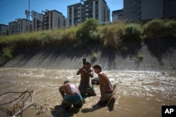 In this Dec. 5, 2017 photo, Angel Villanueva, center, uses a metal bar to break up the mud at the bottom of the polluted Guaire River in Caracas, Venezuela.