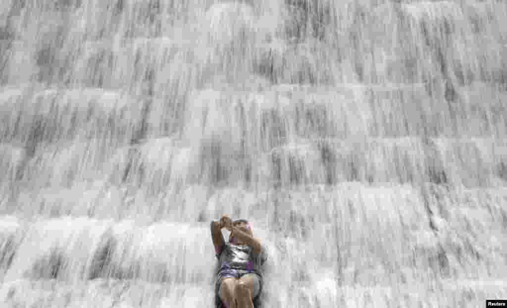 A woman enjoys the water overflowing from a defunct but still watery reservoir called the Wawa Dam in Montalban in Manila, the Philippines.