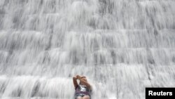 A woman enjoys the water overflowing from a defunct but still watery reservoir in Montalban in Manila. (File)