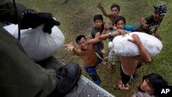 지난 11월 태풍 하이옌 피해 지역 주민들이 미 해군 소속 헬기에서 나눠주는 구호물자를 받고 있다.