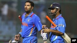 India's Yuvraj Singh (L) and captain Mahendra Singh Dhone walk off the field together after they won their ICC Cricket World Cup group B match against The Netherlands in New Delhi, March 9, 2011