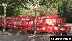 """甲骨文公司在中國裁員,被裁員工抗議示威,橫幅上書寫""""加班時我們全力以赴,裁員時請真情相對"""",""""我們要工作,孩子要上學,為何如此下狠手!""""。(推特圖片)"""