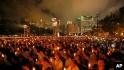 In this June 4, 2019, file photo, thousands of people attend a candlelight vigil for victims of the Chinese government's brutal military crackdown three decades ago on protesters in Beijing's Tiananmen Square at Victoria Park in Hong Kong. (AP Photo/Kin Cheung, File)