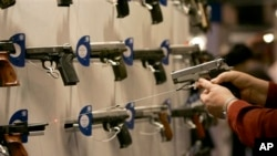 Seorang pengunjung tengah menunjuk salah satu senjata api yang dipamerkan di sebuah pameran senjata di St. Louis, yang diadakan oleh NRA, organisasi pemilik sejata AS (Foto: dok). NRA memberikan rekomendasi untuk memilih dan mempersenjati karyawan sekolah untuk melindungi siwa di Amerika, Selasa (2/4).