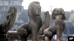 In this photo taken, June 27, 2010, lion statues sit in front of the famed Angkor Wat in Siem Reap province, about 320 kilometers (199 miles) north of Phnom Penh, Cambodia.