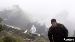 An investigator (back) works near the wreckage of a military plane which crashed near the village of Ouled Gacem in eastern Algeria, about 500km (311 miles) from the capital Algiers on February 12, 2014. The military transport plane carrying members of the Algerian armed forces and their relatives crashed into a mountain, killing 77 people, the worst air disaster in the North African country in a decade. (REUTERS/Louafi Larbi)