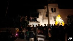 Warga Palestina menyaksikan rumah yang diledakkan milik Amer Abu Aisheh, salah satu dari tersangka penculikan remaja Israel, di Hebron, Tepi Barat (1/7).