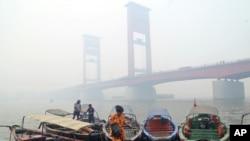 Seorang perempuan di atas kapal dekat Jembatan Ampera di Palembang yang diselimuti kabut asap kebakaran hutan, Palembang, Sumatra Selatan, 29 September 2015. (Foto: AP)