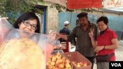記者(左一)拿著一塊剛烤好的「饢」 ,比以往在杜拜吃過的中東烤餅大好幾倍,但製作過程差不多