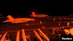 Chiến đấu cơ F/A-18 Super Hornet chuẩn bị cất cánh từ boong tàu bay của tàu sân bay USS George HW Bush (CVN 77) để thực hiện nhiệm vụ tấn công các mục tiêu IS ở Syria.