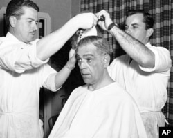 Actor Boris Karloff gets into make up on for his role as ...