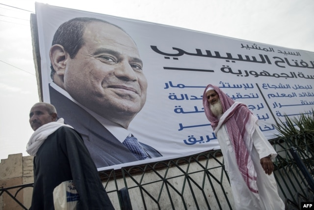 Egyptian men walk past a campaign billboard of Egyptian ex-army chief and leading presidential candidate Abdel Fattah el-Sissi on a pedestrian bridge in Fayyum, some 100 kilometres south of Cairo, May 20, 2014.