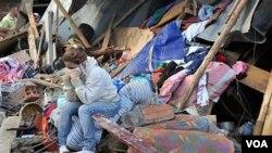 Una mujer muestra su desolación delante de su casa destruida por un deslizamiento de tierra.