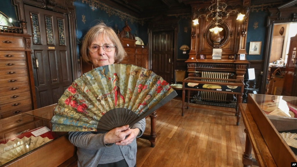 Anne Hoguet, 74, fan maker and director of the hand fan-making museum poses with a a wood roasted hand fan representing the falcon hunt, gouache painting on paper dated from 1880 in Paris, Wednesday, Jan. 20, 2021. (AP Photo/Michel Euler)