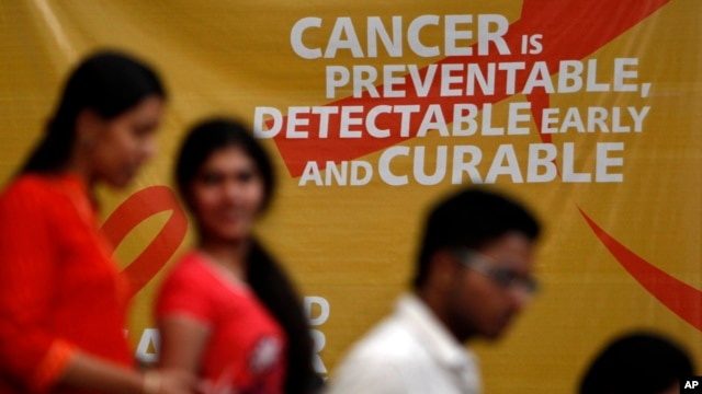 A flash mob participants walk in front of a hoarding spreading awareness on cancer in Hyderabad, India, February 3, 2012.