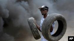 Un manifestant tient des pneus que son groupe utilise dans une barricade enflammée à Bujumbura, Burundi. jeudi 30 avril 2015