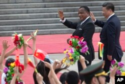 FILE - Chinese President Xi Jinping, right and Republic of Congo President Denis Sassou Nguesso wave as they walk past Chinese children waving flags and flowers to welcome them at a welcome ceremony held outside the Great Hall of the People in Beijing, China, July 5, 2016.