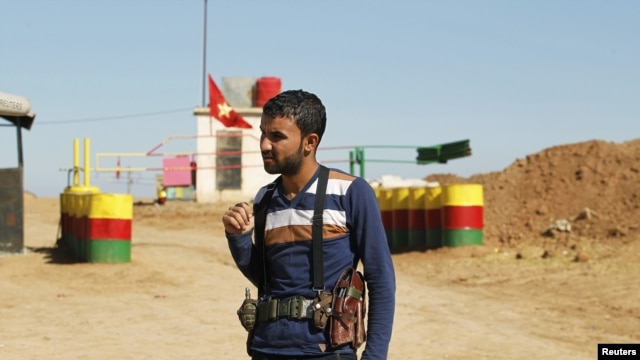 An officer of the Syrian Kurdish Democratic Union Party (PYD) stands guard near the Syrian-Iraq border, October 31, 2012.