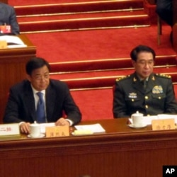 中共中央政治局委员,重庆市委书记薄熙来(前左一)在人大主席台就座