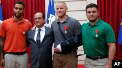 From the left, Anthony Sadler, a senior at Sacramento University in California, French President Francois Hollande, U.S. Airman Spencer Stone, and Alek Skarlatos a U.S. National Guardsman from Roseburg, Oregon pose for a photo.