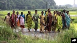 Indian women laborers return after a days work at a paddy field. Indians have been desperately waiting for the long-delayed deluge of this year's monsoon, July 24, 2012.