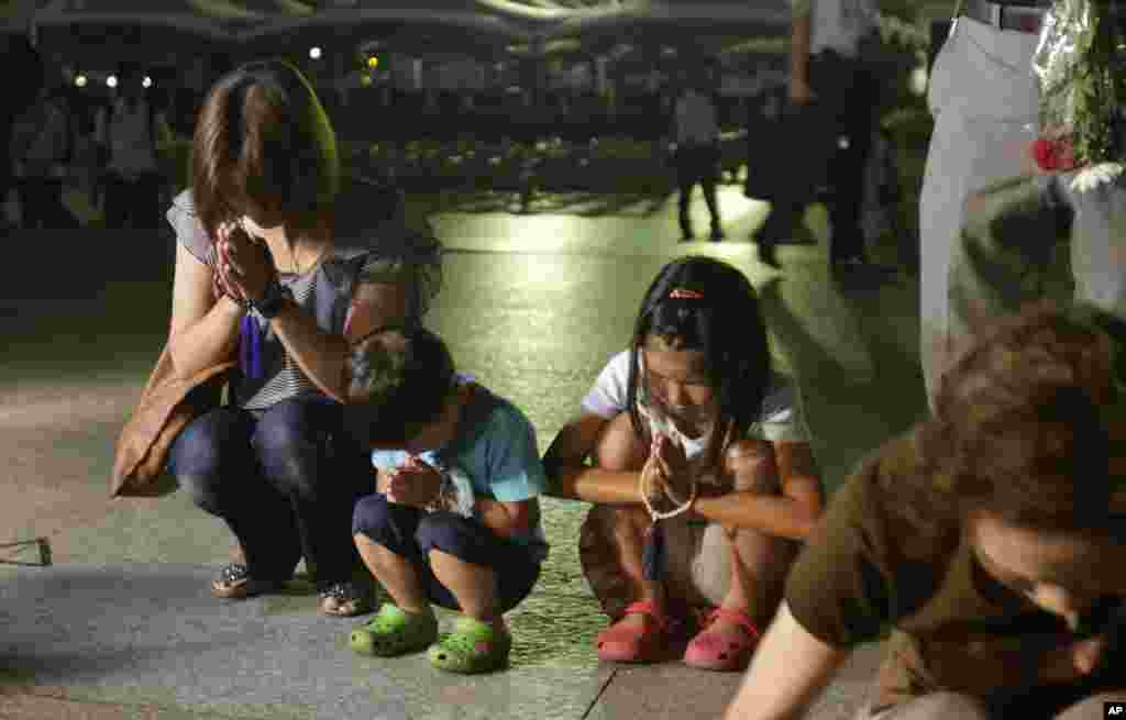 People pray for the atomic bomb victims at the Hiroshima Peace Memorial Park, August 6, 2013.