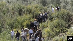 Syrians cross the border into Lebanon as they flee the violence in the Syrian village of Talkalakh, in the Wadi Khaled area, about one kilometer (0.6 miles) from the Lebanon-Syria border, north of Lebanon, May 16, 2011