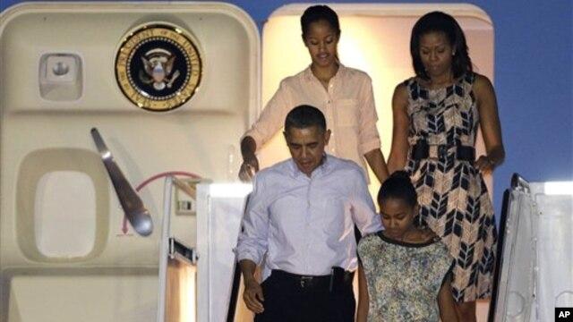 Presiden Barack Obama dan keluarga saat tiba di Honolulu untuk memulai liburan mereka (22/12). (AP/Gerald Herbert)