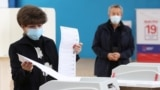 A woman casts her ballots at a polling station on the last day of three-day long parliamentary elections in Moscow, Russia, Sept. 19, 2021.