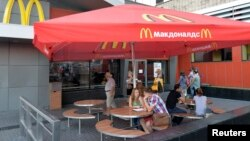 People sit outside a closed McDonald's restaurant in Moscow, Aug. 20, 2014.