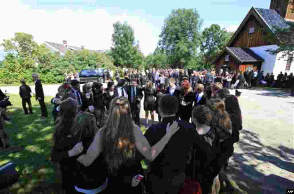 Mourners gather in a circle to console themselves prior to the funeral procession of Bano Abobakar Rashid, 18, the first victim of the shooting rampage at Utoeya to be buried, during her funeral at a church in Nesodden, near Oslo, Norway, Friday July 29,