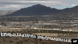 "FILE - Sunland Park, New Mexico, is seen over the U.S. border fence as a protester finishes painting the Spanish slogan ""Neither delinquents nor illegals, we are international workers"" on the Anapra, Mexico, side of the fence, Feb. 26, 2017."
