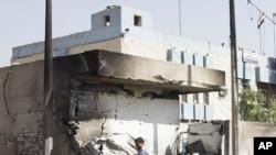 一名伊拉克警察10月12日在巴格达一个被汽车炸弹炸毁的警察局爆炸现场