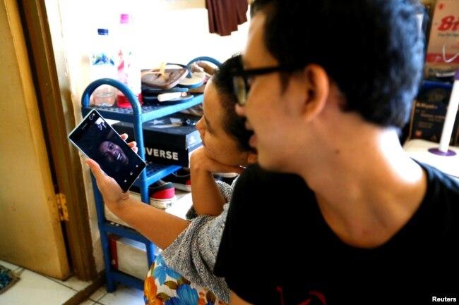 Beberapa penghuni kos sedang berbicara dengan kerabat melalui panggilan video usai salat Ied untuk merayakan Idul Fitri di Jakarta, di tengah pandemi virus corona (Covid-19), 24 Mei 2020. (Foto: Reuters)