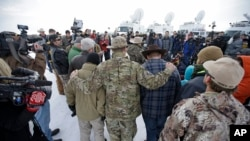 FILE - Members of the group occupying the Malheur National Wildlife Refuge headquarters hug after Ammon Bundy, center, left, one of the sons of Nevada rancher Cliven Bundy, spoke with reporters during a news conference Monday, Jan. 4, 2016, near Burns, Oregon.