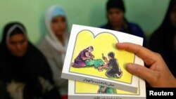 FILE - A counselor holds up cards used to educate women about female genital mutilation (FGM) in Minia, June 13, 2006.