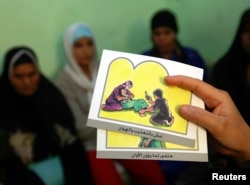 Консультант тримає карти, які використовуються, щоб навчати жінок про практику обрізання, в Мінії, Єгипет.