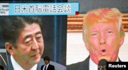 A man walks past a street monitor showing Japan's Prime Minister Shinzo Abe (L) and U.S. President Donald Trump in a news report about their telephone conference on North Korea's threat, in Tokyo, Sept. 3, 2017.