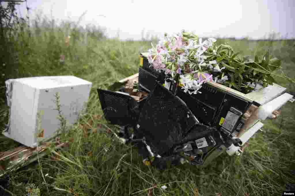 Flowers lie on debris from a Malaysian Airlines Boeing 777 plane which was downed on Thursday near the village of Rozsypne, in the Donetsk region, Ukraine.