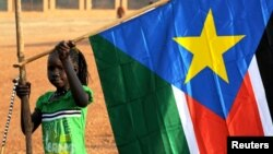 A girl holds a South Sudan flag on January 30 during the announcement of the preliminary results of voting on independence.