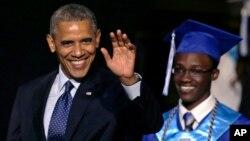 El presidente Barack Obama, acompañado de un graduando, saluda a su llegada a la ceremonia de graduación de la escuela Worcester Technical High School, en Massachusetts.