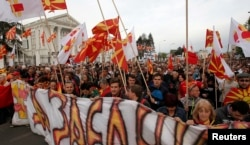 FILE - Protesters march through a street in Skopje, Macedonia, April 3, 2017.
