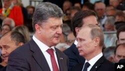 Presiden Ukraina Petro Poroshenko dan Presiden Rusia Vladimir Putin saat menghadiri acara peringatan Perang Dunia di Perancis Juni lalu (foto: dok).