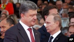Ukraine's President-elect Petro Poroshenko, left, walks past Russian President Vladimir Putin during the 70th anniversary commemoration of D-Day in Ouistreham, western France, June 6, 2014.