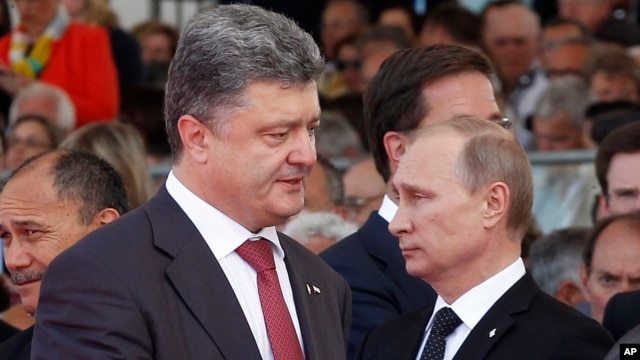 Ukraine's President-elect Petro Poroshenko, left, walks past Russian President Vladimir Putin during the 70th anniversary commemoration of D-Day in Ouistreham, western France, June 6, 2014.