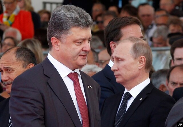 Ukraine's President-elect Petro Poroshenko, left, walks past Russian President Vladimir Putin during the commemoration of the 70th anniversary of the D-Day in Ouistreham, western France, June 6, 2014.